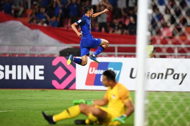 Thailand's forward Supachai Jaided celebrates with a leap over Singapore goalkeeper Hassan Sunny after scoring the second goal of the match in the 23rd minute. (AFP photo)