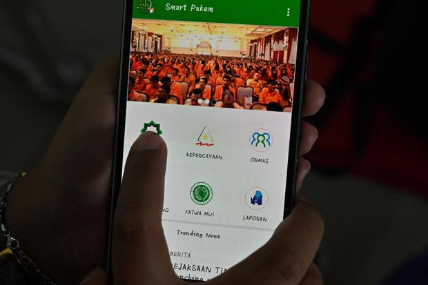 An Indonesian woman shows a newly launched smartphone application called