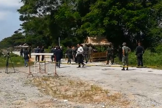 Officers cordon off the scene of a shooting at a weekend market in Thepha district, Songkhla.  (Photo grabbed from a video submitted by Abdulloh Benjakat)