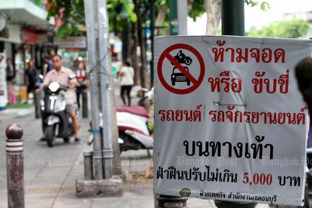 Signs forbidding vehicles on the pavements are so common that no one pays them much heed - even though they promise fines on the spot of 5,000 baht. (File photo)