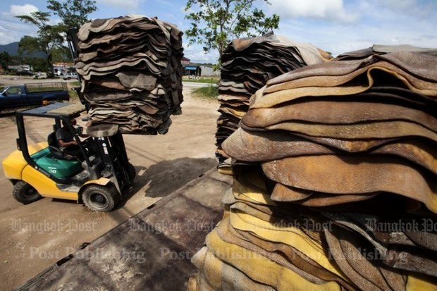 Rubber warehouse workers stack latex sheets as part of the preparation for sale. More aid to farmers is on the way. (Bangkok Post photo)