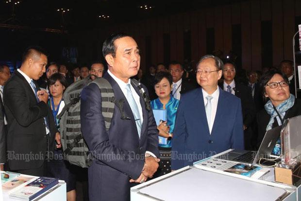 Prime Minister Prayut Chan-o-cha, centre, tries an