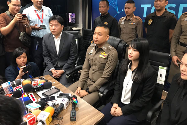 Cherprang Areekul, 22, seated second right, speaks to reporters at the Technology Crime Suppression Division in Bangkok after filing her complaint on Tuesday. (Photo by Wassayos Ngamkham)