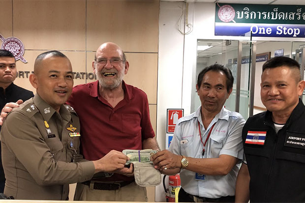 Smiling American tourist Jerry Allen Hart, 74, thanks taxi driver Veeraphol Klamsiri, 57, for returning a bag containing 98,000 US dollars -- about 320,000 baht -- left in his cab, as Suvarnabhumi airport police look on, on Tuesday night. (Photo by Sutthiwit Chayutworakan)