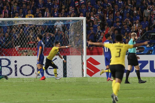 A missed penalty by forward Adisak Kraisorn (left) put Malaysia through to the Suzuki Cup final. (Photos by Wichan Charoenkiatpakul)