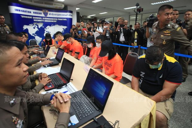 This American (right) and six Chinese (in orange) were arrested on Friday and Saturday when they were trying to sit an American College Testing (ACT) exam for other people using fake passports. Immigration Bureau chief Pol Lt Gen Surachate 'Big Joke' Hakparn is at far right. (Photo by Somchai Poomlard