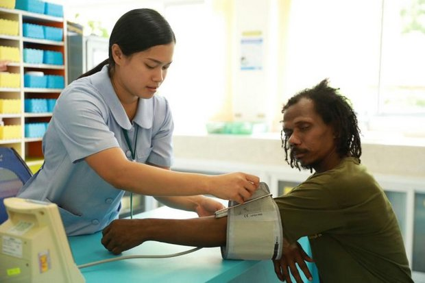 A health care worker treats an indigenous Mani man in remote Naree district of Phattalung province. The government says changes are imminent in universal health care. (Photo courtesy National Health Security Office)
