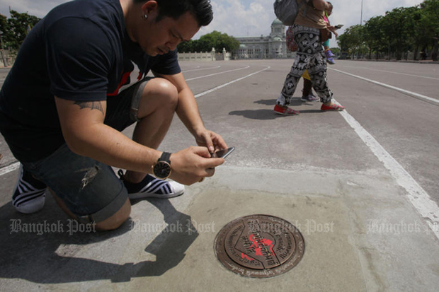 A journalist photographs a new plaque fitted into the road at the Royal Plaza on April 14, 2017. It replaced the Khana Ratsadon memorial plaque commemorating the 1932 Siamese Revolution. (Photo by Apichit Jinkul)
