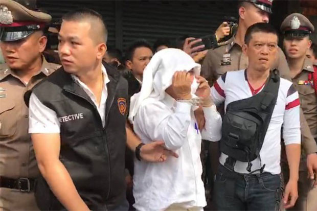 Police escort suspect Pipatpongpat Suksawatpipat, 59, for a crime re-enactment at a shop in Bang Rak district on Saturday morning. The former jewellery trader was arrested in Chanthaburi while trying to flee to Cambodia. (Photo from @Policenewspage Facebook page)