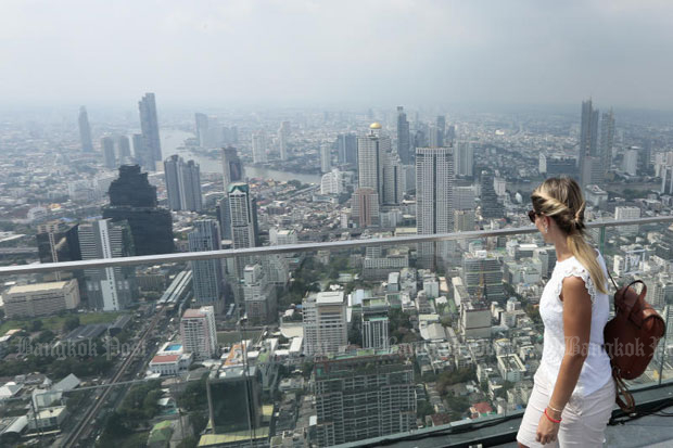 A tourist enjoys the view from the King Power Mahanakhon Building in Bangkok. International cost of living surveys rank the capital among the 100 most expensive cities for expatriate workers for the first time this year. (Photo by Patipat Janthong)