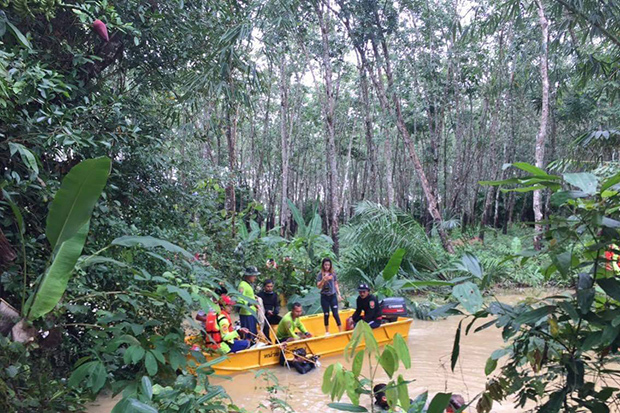 Rescuers recover the body of a 14-year-old boy from a small canal in Cha-uat district of Nakhon Si Thammarat on Tuesday. (Photo by Nujaree Raekrun)
