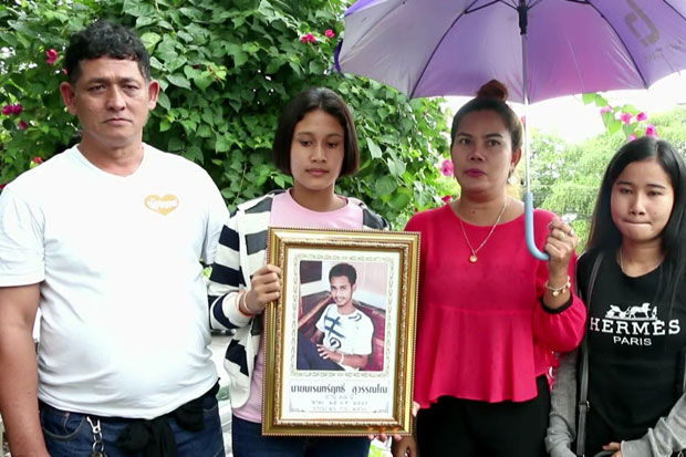 Family members of Songkhla native Narenrit Suwanno, 17, on Wednesday hold his picture at the Trang provincial court. where death and life imprisonment sentences were laid down for his murder by a gang of policemen last year. (Photo by Methee Muangkaew)