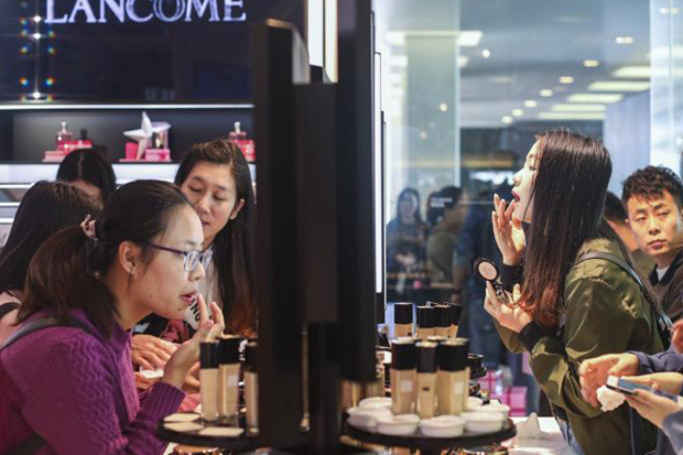 Shoppers in Hong Kong try out some cosmetics as they shop for gifts ahead of the Christmas holiday. (South China Morning Post photo)