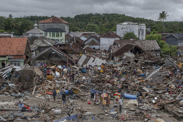 People inspect the damage at a tsunami-ravaged village in Sumur, Indonesia, Monday, Dec 24, 2018. Doctors are working to help survivors and rescuers are looking for more victims from a deadly tsunami that smashed into beachside buildings along an Indonesian strait. The waves that swept terrified people into the sea Saturday night followed an eruption on Anak Krakatau, one of the world's most infamous volcanic islands. (AP photo)