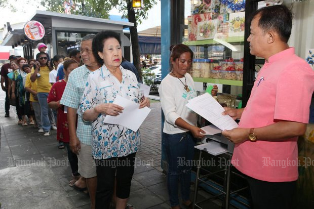 Activist Srisuwan Janya (right) greets a line of people eager to sign his petition aiming to impeach and remove the entire National Anti-Corruption Commission (NACC). (Photo by Apichit Jinakul)