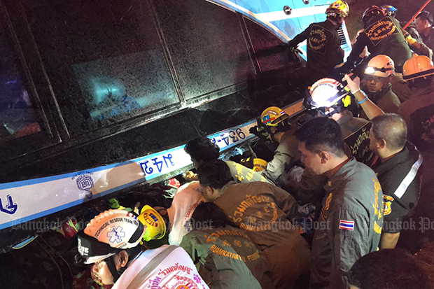 Rescuers help to extract stranded passengers from the double-decker bus that turned upside down in Khlong Luang district in Pathum Thani on Sunday morning. (Photo by Pongpat Wongyala)