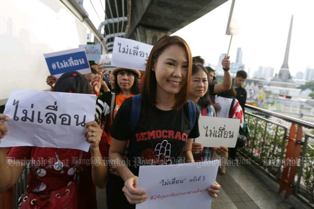 Nuttaa 'Bow' Mahattana and other protesters march on the skywalk at Victory Monument on Sunday to show their opposition to postponement of the election. (Photo by Wichan Charoenkiatpakul)