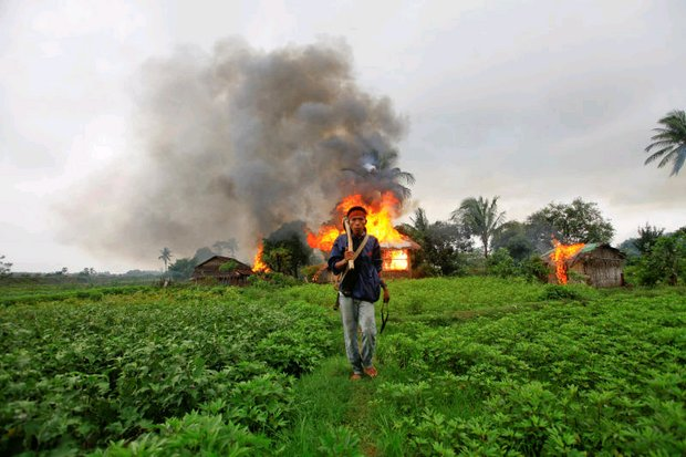 An ethnic Rakhine man holds homemade weapons as he walks in front of houses that were burnt during fighting between Buddhist and Muslim Rohingya communities in 2012. (Reuters photo)