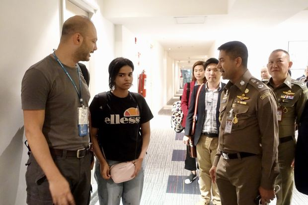 Rahaf Mohammed al-Qunun (second from left) is escorted by Thai immigration police chief Lt Gen Surachate Hakparn (second from right) and UNHCR officials from her hotel room after Thailand agrees to admit her for evaluation by UNHCR. (Photo supplied by Thai police)