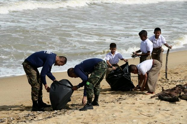 Students and soldiers hit the beaches together on Monday in Narathiwat province to clean up debris from Tropical Storm Pabuk. (AFP photo)