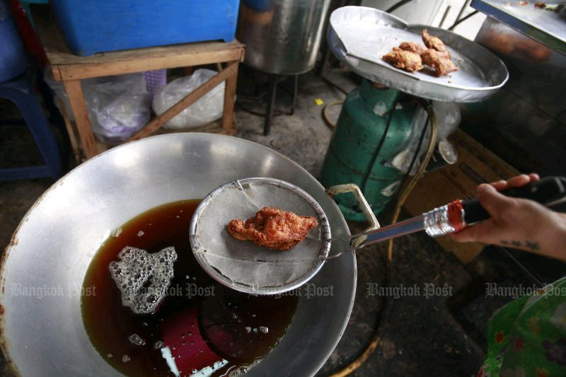 A vendor removes a (legal) deep-fried chicken from his wok. The ban on 'partially hydrogenated oils' has taken effect smoothly, with praise from all parties. (Photo by Pornprom Satrabhaya)