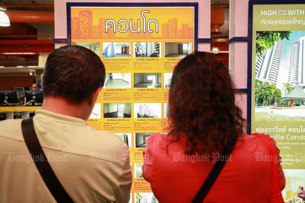 A couple check out condominium offerings at a Bangkok house-and-condo sale. The Bank of Thailand warned Thursday of a possible condo glut this year on diminishing demand. (File photo)