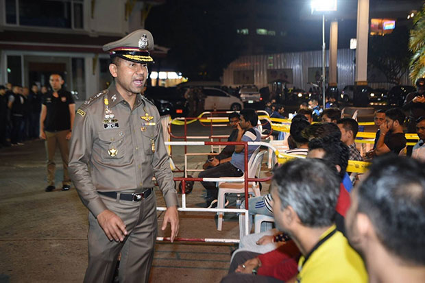 Pol Lt Gen Surachate Hakparn, commissioner of the Immigration Bureau, talks to some of the foreigners caught during Friday morning's