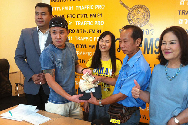 Taxi driver Somporn Joynusaeng, right, returns 153,000 baht in cash to a 29-year-old Japanese tourist, left, who left his bag in the cab. The return of the money was  witnessed by executives of FM91 traffic radio station on Friday. (Photo taken from @Thailandlostandfoundfm91 Facebook page)