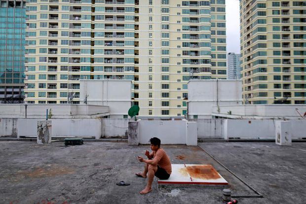 A migrant worker from Myanmar sits on a roof of a building in Bangkok on Sept 1 last year. (Reuters photo)
