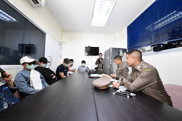 Immigration chief Surachate Hakparn, right, talks to suspected operators of an online gambling site at Prawet police station in Bangkok on Tuesday night. (Photo supplied)