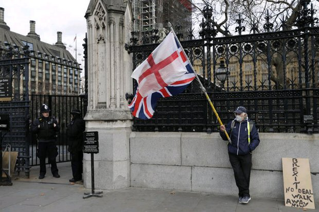 A lone protester holds flags of England and Britain at an entrance to the UK parliament in London. (AP photo)