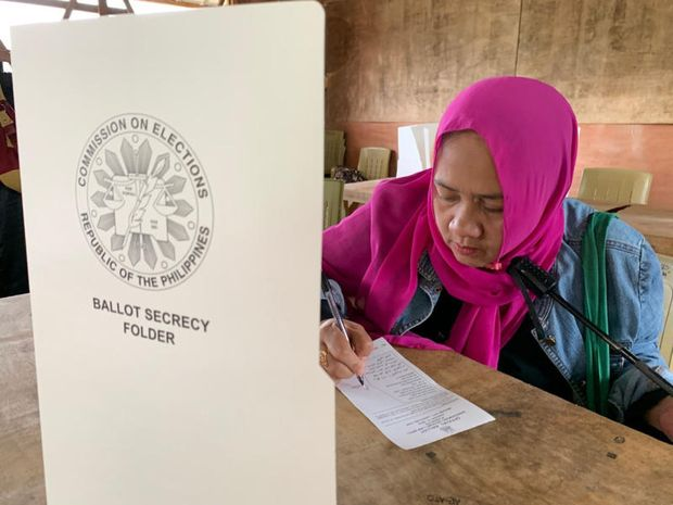 A Muslim woman completes a ballot paper in a referendum at the Marawi Sagonsongan elementary school-turned polling station in Marawi, Lanao del Sur province, southern Philippines, on Monday. Monday. (AP photo)