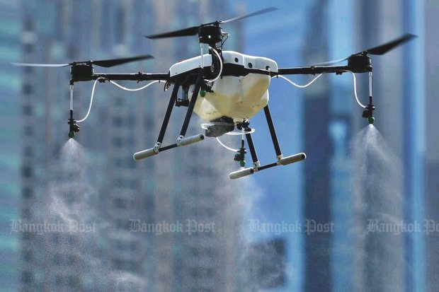 A drone produces water and non-hazardous chemical spray to diffuse the dust particles at Vachirabenjatas Park, also known as Rot Fai Park, in Chatuchak district during a test run on Tuesday. (Photo by Patipat Janthong)