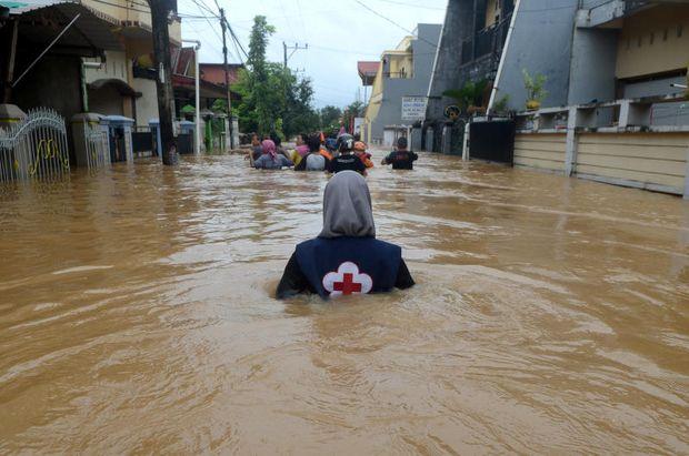 A volunteer wades through floods at a residential area in Makassar, South Sulawesi, Indonesia, on Wednesday. (Antara Foto/Sahrul Manda Tikupadang/ via REUTERS)