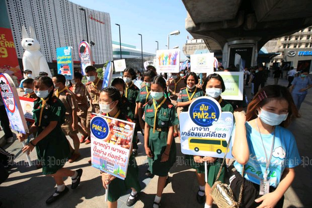 The first act by Bangkok governor Pol Gen Aswin Kwanmuang after the government passed him control of the pollution crisis was to get primary school children on busy Rama I Road near Siam Square to carry signs printed by City Hall in order to 'raise awareness' of the unhealthy PM2.5 smog. (Photo by Somchai Poomlard)