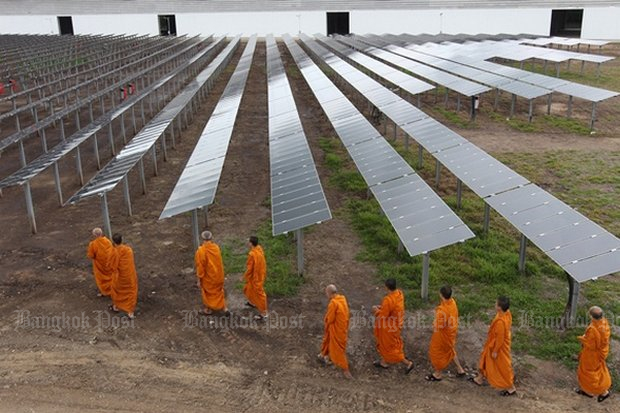 Monks walk past a solar farm on their way to the temple after morning alms rounds. The latest version of a 20-year energy plan increases the importance of renewable energy. (File photo)