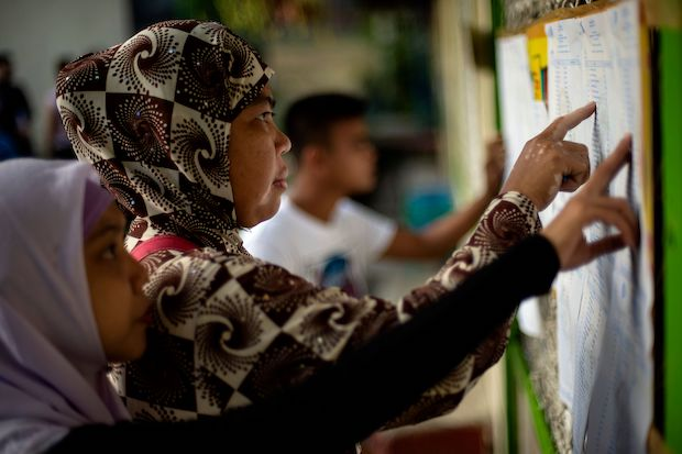 Women look for their names on a voters' list at a polling station in Maguindanao, on the southern island of Mindanao, during voting this week to ratify the passage of the Bangsamoro Organic Law. (AFP Photo)