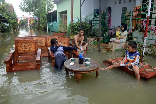 Residents sit as they clean up their property following floods at a residents area in Makassar, South Sulawesi, Indonesia, on Friday. (Antara Foto)