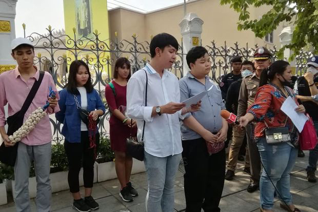 Tanawat Wongchai (front row, left) and Parit Chiwarak (front row, second left) read an open letter to Prime Minister Prayut Chan-o-cha at a Government House gate on Saturday before they were taken to a police station. (Photo from Facebook@ballbanofficial)