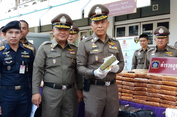 Deputy police chief Gen Chalermkiat Srivorakhan (holding a marijuana brick) and other senior police officers show the evidence seized from recent drug busts in the Northeast on Sunday. (Photo by Prasit Tangprasert)