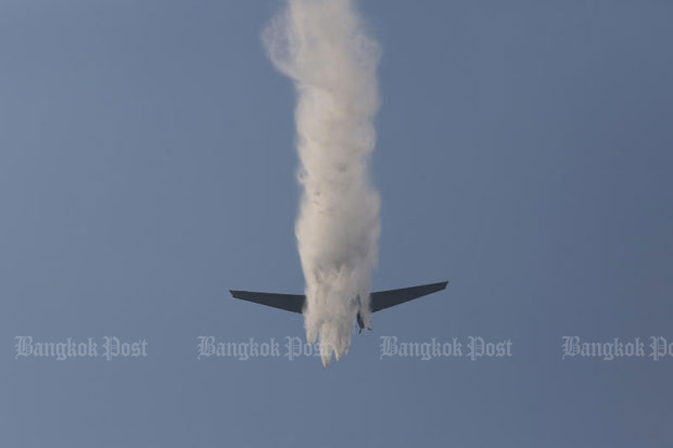 A light plane showers water on Chatuchak district, Bangkok, on Saturday. The Pollution Control Department reported on Monday morning that toxic dust levels had fallen to within