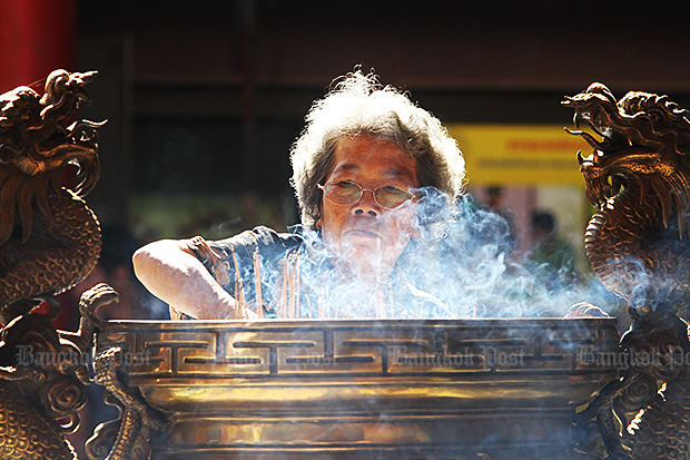 While some Thai-Chinese descendants have opted to burn fewer incense sticks and less joss paper in order not to worsen Bangkok's smog crisis, the old generation insists on keeping the tradition. (Photo by Apichit Jinakul)