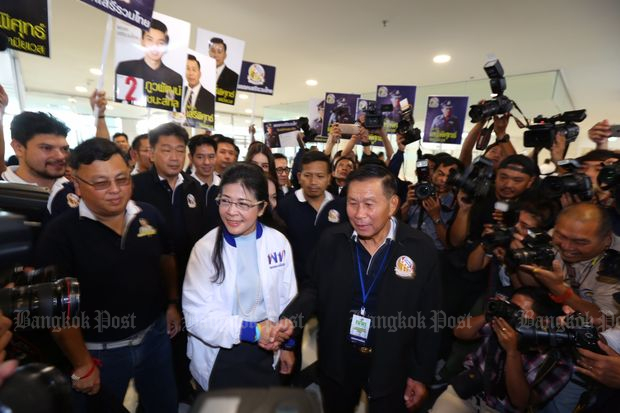 Khunying Sudarat Keyuraphan of Pheu Thai Party and Pol Gen Seripisuth Temiyavej of the Thai Liberal Party shake hands as they meet at the Election Commission's office to submit their party lists on Tuesday. (Photo by Kitja Apichonrojarek)