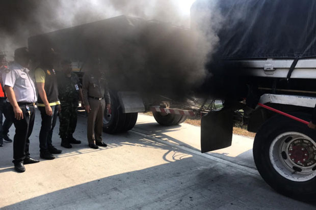 A trailer truck belches black exhaust smoke after being stopped for an emissions test in Ayutthaya province on Friday. (Photo by Sunthon Pongpao)