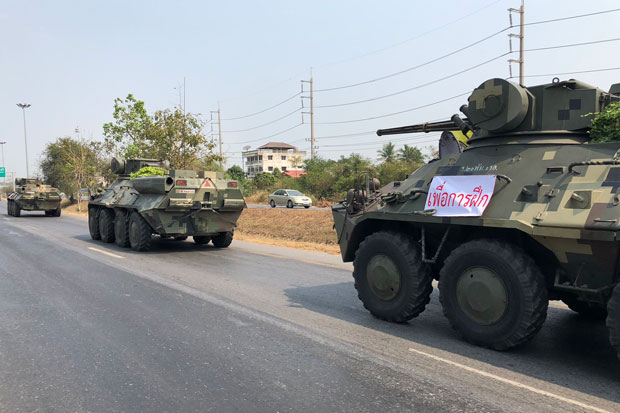 A convoy of armoured cars from Chon Buri, Prachin Buri and Sa Kaeo provinces heads to Sara Buri province for military exercises. The banner attached to the vehicles states