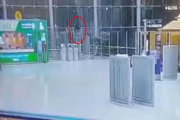 A security camera captured the moment when Mikhail Sinitsyn climbed a safety glass wall at Suvarnabhumi airport on Monday morning. (Photo from Suvarnabhumi Airport police)