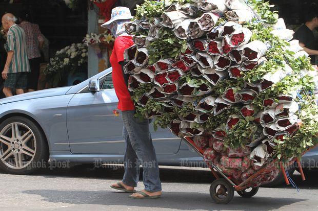 A man moves flowers to shops at Pak Khlong Talat fresh market in Bangkok on Tuesday. (Photo by Apichart Jinakul)