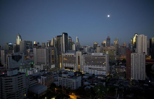 Skyscrapers are illuminated by moonlight at dawn on Sept 26, 2018 in Bangkok. Construction of luxury high rise residences is booming in the city, driven partly by strong demand from wealthy Chinese and other foreign investors, contributing to economic growth. (AP file photo)
