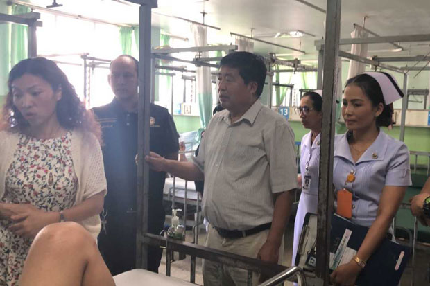 Officials talk to Chinese tourist Li Yuanzheng at Surat Thani Hospital in Surat Thani province on Monday before he was taken to Samui airport for a flight to China. (Photo by Supapong Chaolan)