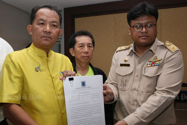 Srisuwan Janya (left), secretary-general of the Association for the Protection of the Constitution, submits a petition to an Election Commission official at the EC's office at Government Complex on Monday. (Photo by Apichit Jinakul)